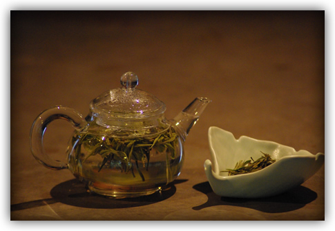 tea steeping in glass pot with ginkgo leaf-shaped ceramic dish of dry leaf