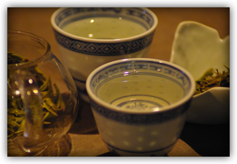 the liquor in two little ceramic cups flanked by the infusion in the glass pot and dry leaf in the ginkgo dish
